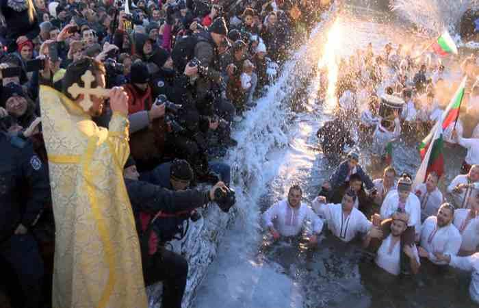 Церковный служитель бросает крест в воду